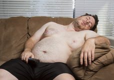 Lazy fat guy watching TV. While watching TV this lazy fat guy fell asleep royalty free stock image