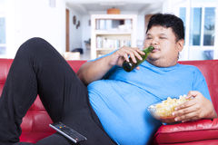 Lazy fat man at home. Overweight man sitting lazy on sofa while drinking beer and eat snack Royalty Free Stock Photos