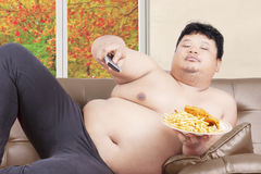 Lazy fat man watches tv in autumn Stock Photos