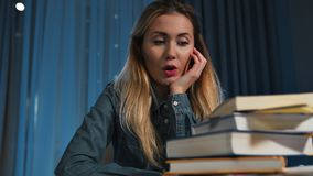 Lazy female student in a denim shirt, surprised and concerned about a lot of books. A lot of work. Close-up. stock video footage