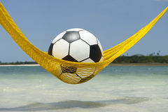 Lazy Football Soccer Ball Relaxing in Beach Hammock Stock Images
