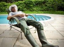 Lazy gardener. Lazy senior gardener napping  poolside Stock Photos