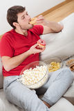 Lazy guy on a couch with food Stock Photo