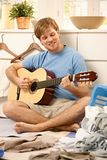 Lazy guy playing guitar Royalty Free Stock Photos