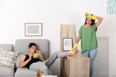 Lazy husband lying on sofa and his wife cleaning. At home stock photos