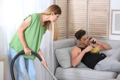 Lazy husband lying on sofa and his wife cleaning royalty free stock photography
