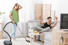 Lazy husband watching TV and his wife cleaning royalty free stock photo