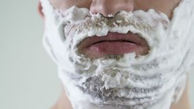 Lazy male applying shaving foam in front of mirror, skincare and hygiene. Stock footage stock video