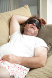 Lazy Man Asleep on Couch. Lazy, unemployed man asleep on the couch, unshaven and in his underwear Stock Photos