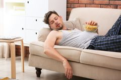 Lazy man with bowl of chips sleeping on sofa. At home royalty free stock photography