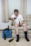Lazy Man Couch Potato Slob Drunk With TV Remote. This man is in need of a life! We have here a male being the typical lazy slob known as the couch potato who is royalty free stock image