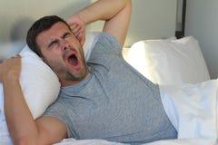 Lazy Man que bosteza en cama fotografía de archivo