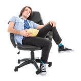 Lazy Man que se sienta en butaca con un cuenco de palomitas de maíz Foto de archivo