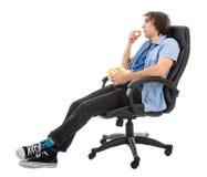 Lazy Man que se sienta en la butaca que come la palomitas de maíz, aislada sobre blanco Imágenes de archivo libres de regalías