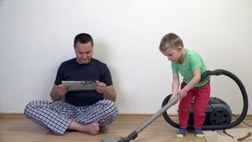 Man reads newspaper while kid is cleaning house with vacuum cleaner