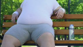 Lazy man sitting on bench stroking his big fat belly instead of going for sport stock video footage
