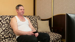 Lazy man sitting  on couch and watching television stock video