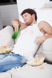 Lazy man sitting on couch. And watching tv Royalty Free Stock Photo