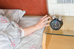 Lazy man using a hand to grab a ringing clock. In noon time Royalty Free Stock Images