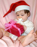 Lazy X-mas. Little Santa checking her presents royalty free stock photo