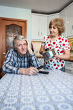 Lazy mature husban lounges in the kitchen, his wife makes help on housework Royalty Free Stock Image