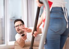 Woman vacuuming while man watching tv Royalty Free Stock Photos