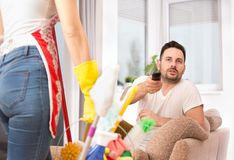 Woman mopping floor while man watching tv. Lazy men with remote control trying to watch tv behind wife who mopping floor Royalty Free Stock Photo