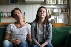 Lazy millennial couple getting bored at home sitting on sofa. Young funny disinterested girl and guy feeling boredom on dull tedious monotonous weekend Royalty Free Stock Photo