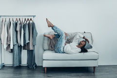 Lazy mood. Thoughtful young woman in casual wear touching her head with hand and putting feet up while lying on sofa at home near her clothes hanging on the Stock Photography