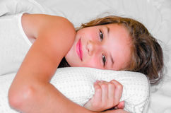 Lazy morning. Young happy girl laying on bed while waking up Stock Image