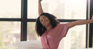 Lazy morning. Young well slept african american woman in pajamas stretching, sitting in bed, waking up
