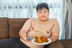 Lazy overweight asian male with fast food and watching televisio Royalty Free Stock Photos