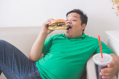 Lazy overweight man eating hamburger while laying on a couch Royalty Free Stock Photography