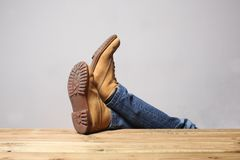 Free Lazy Person Concept: Man`s Legs Wearing  Blue Jeans  Of Desert Boots Rest On A Wooden Table With Copy Space For Your Text Royalty Free Stock Photos - 145117548