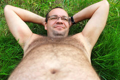 Lazy person. A man with a big belly lies on the grass stock photo