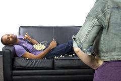 Lazy Roommate. Female angry at lazy male roommate making a mess Royalty Free Stock Images