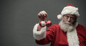 Lazy Santa Claus holding Christmas balls. Lazy Santa Claus with sarcastic expression, he is holding two Christmas balls Royalty Free Stock Image