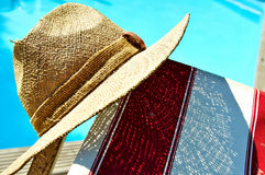 Lazy Sunday Afternoon. Straw hat, deck chair and swimming pool royalty free stock image