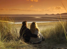 Lazy Sunday Afternoon. Couple hugging on sand-dunes watching sunset Stock Images