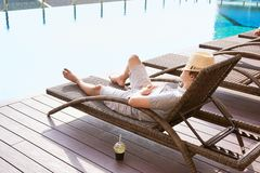 Lazy time. Asian guy sleeping on the couch swimming pool in summ. Er Royalty Free Stock Photography