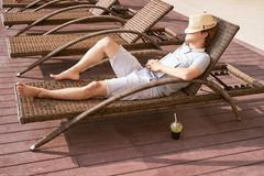 Lazy time. Asian guy sleeping on the couch swimming pool in summer royalty free stock photo