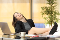 Lazy or tired businesswoman sleeping at work. With the legs over the table at office Stock Image