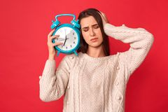 Lazy to Wake Up. Young woman standing isolated on red with alarm clock touching head unhappy royalty free stock images