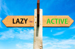Lazy versus Active messages, Healthy Lifestyle conceptual image. Wooden signpost with two opposite arrows over clear blue sky, Lazy versus Active messages Stock Photos