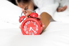 Lazy wake up in morning. Irritated young woman putting her alarm clock off in the morning, lazy wake up in morning. Relaxing concept Royalty Free Stock Image
