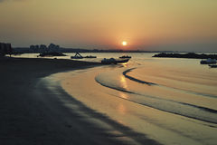 Lazy waves at the sunset. Calm, slow and lazy waves caressing the small sandy beach at beautiful sunset Stock Image