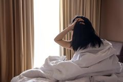 A Lazy Woman with Messy Hair sitting on White Bed and Looking O Royalty Free Stock Image