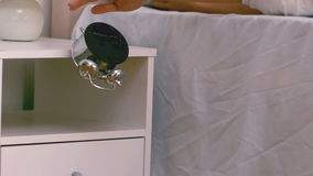 Lazy woman pushing down her alarm clock stock footage