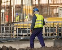 Slacker is walking with  cigarettes through the construction sit. Lazy worker is walking with  cigarettes through the  construction site Royalty Free Stock Photos