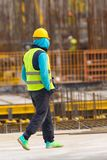 Lazy worker is walking with hands in pockets through the  constr. Twiddler is walking with hands in pockets through the  construction site Stock Photos